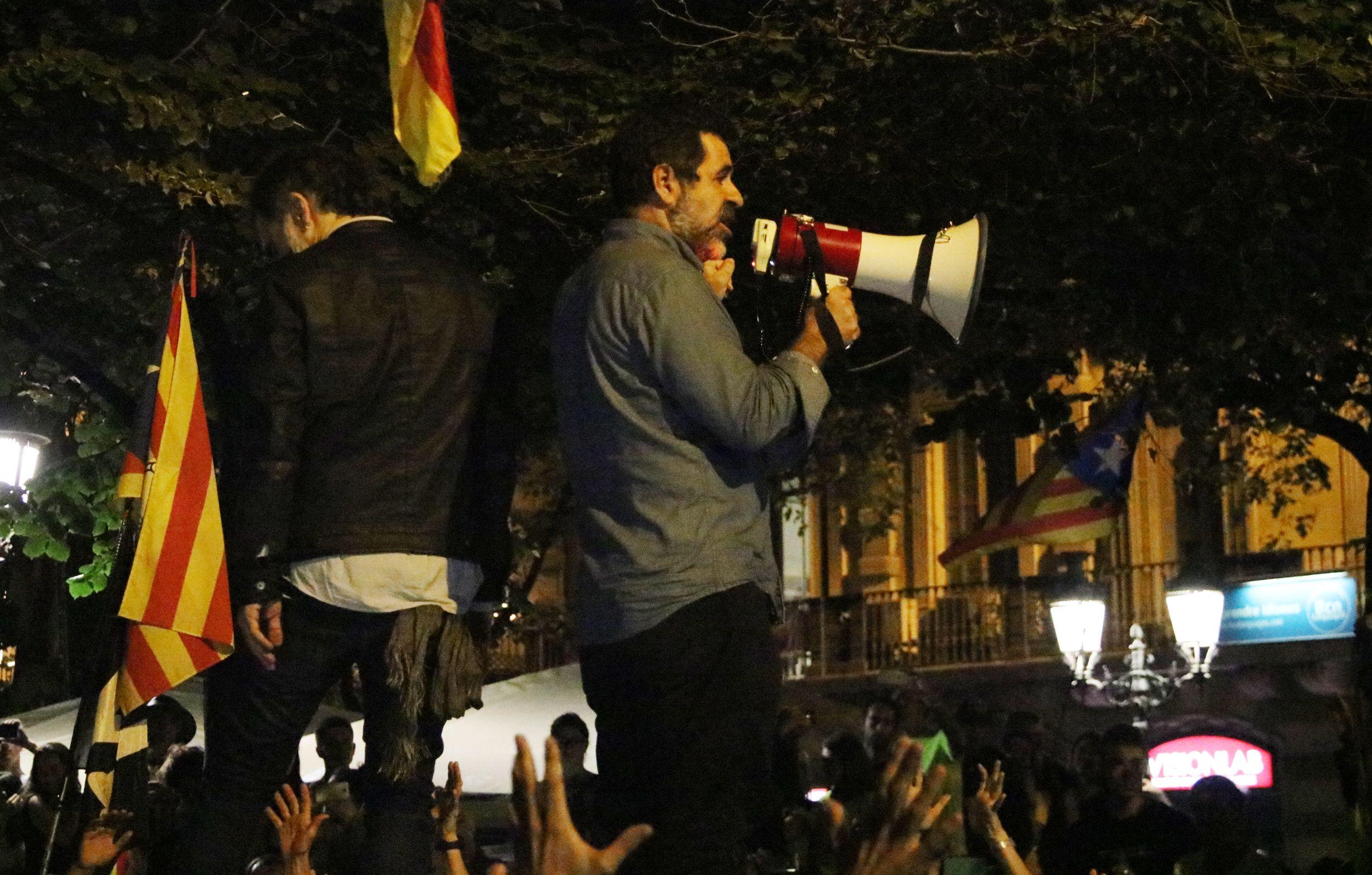 Jordi Sànchez de perfil, i Cuixart d'esquena, sobre el vehicle de la Guàrdia Civil