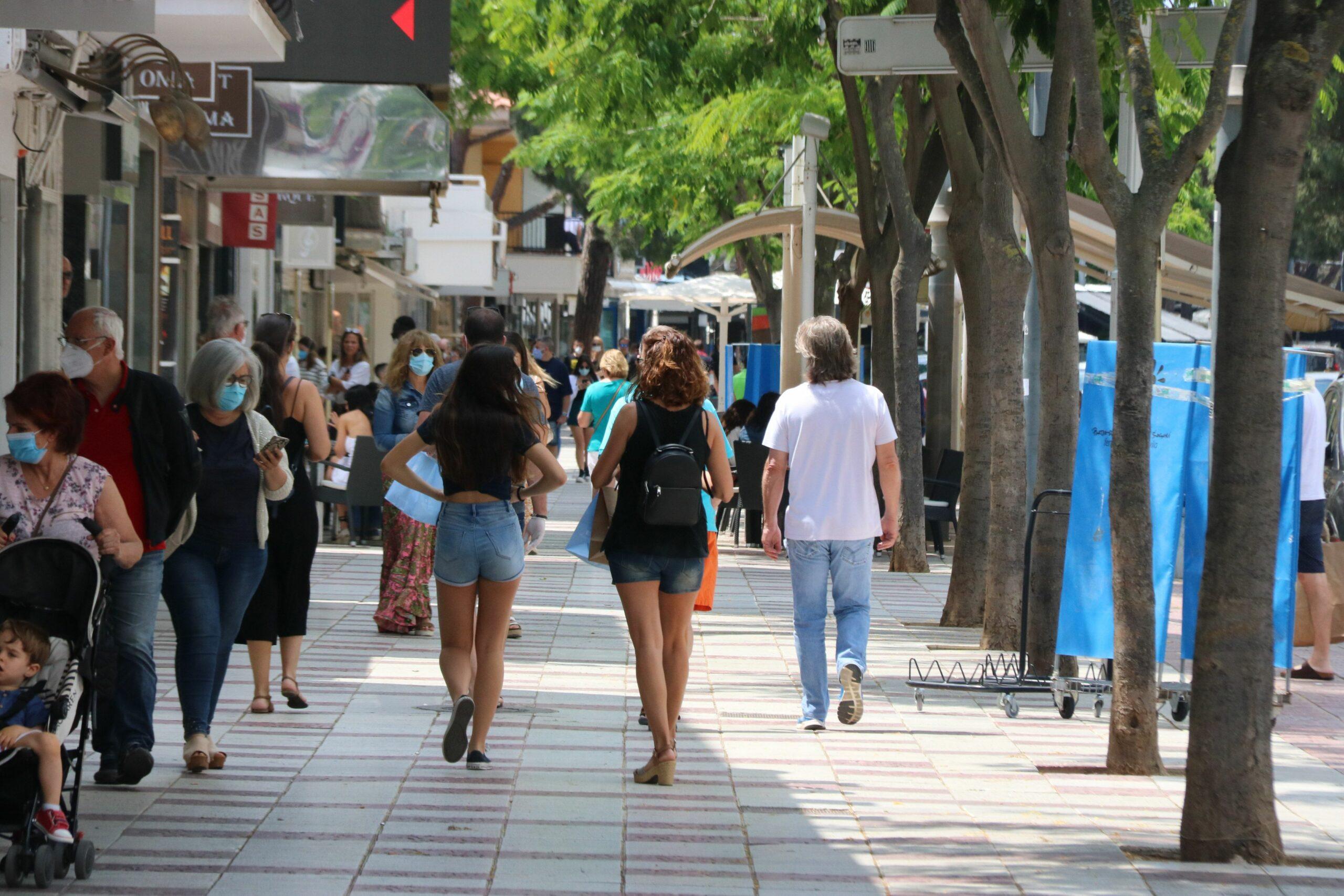 L'Avinguda Cavall Bernat de Platja d'Aro amb diverses persones passejant entre els comer?os