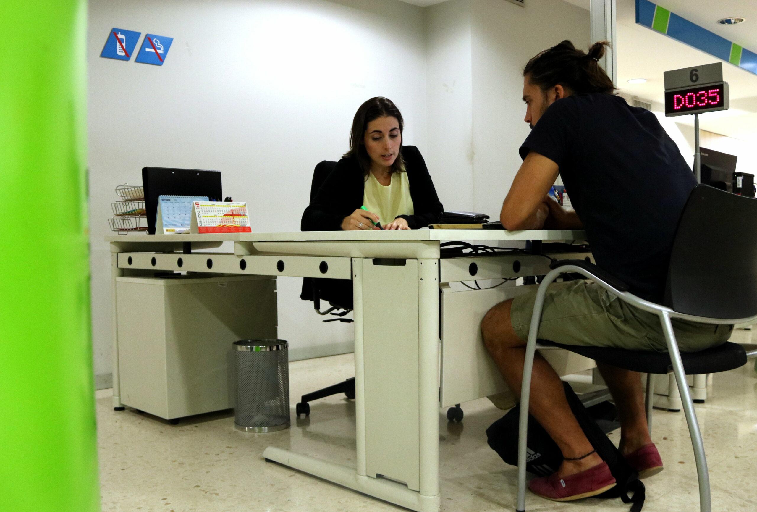 Un ciutadà atén les explicacions d'una treballadora del Servei d'Ocupació de Catalunya | ACN