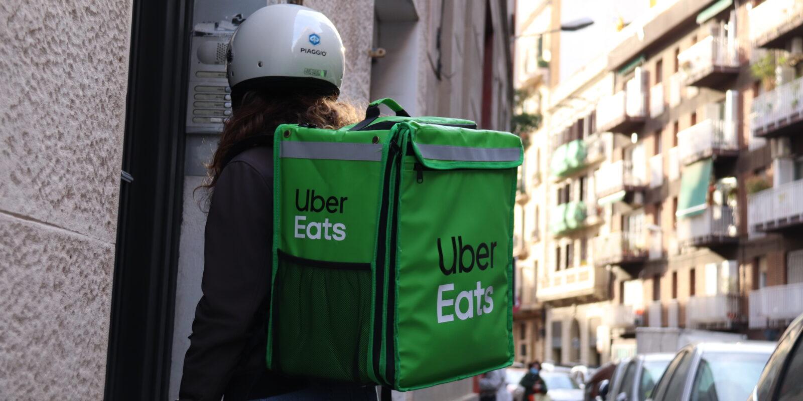 Pla curt d'una repartidora d'Uber Eats esperant per entrar a entregar una comanda a un domicili, el 8 d'abril del 2021 (Horitzontal)