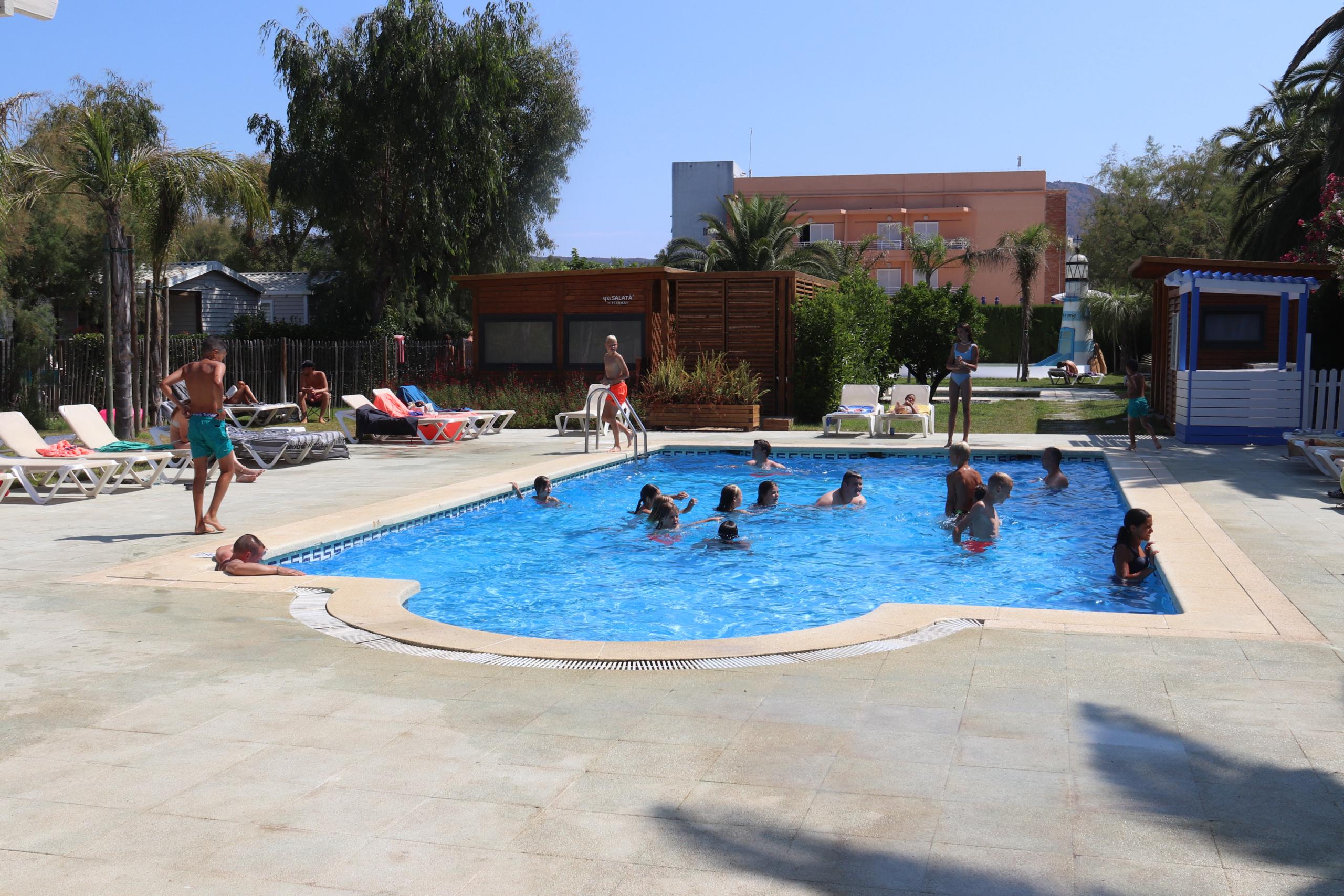 La piscina del càmping Salatà de Roses amb diversos turistes jugant a l'aigua i d'altres estirats a la tovallola   ACN