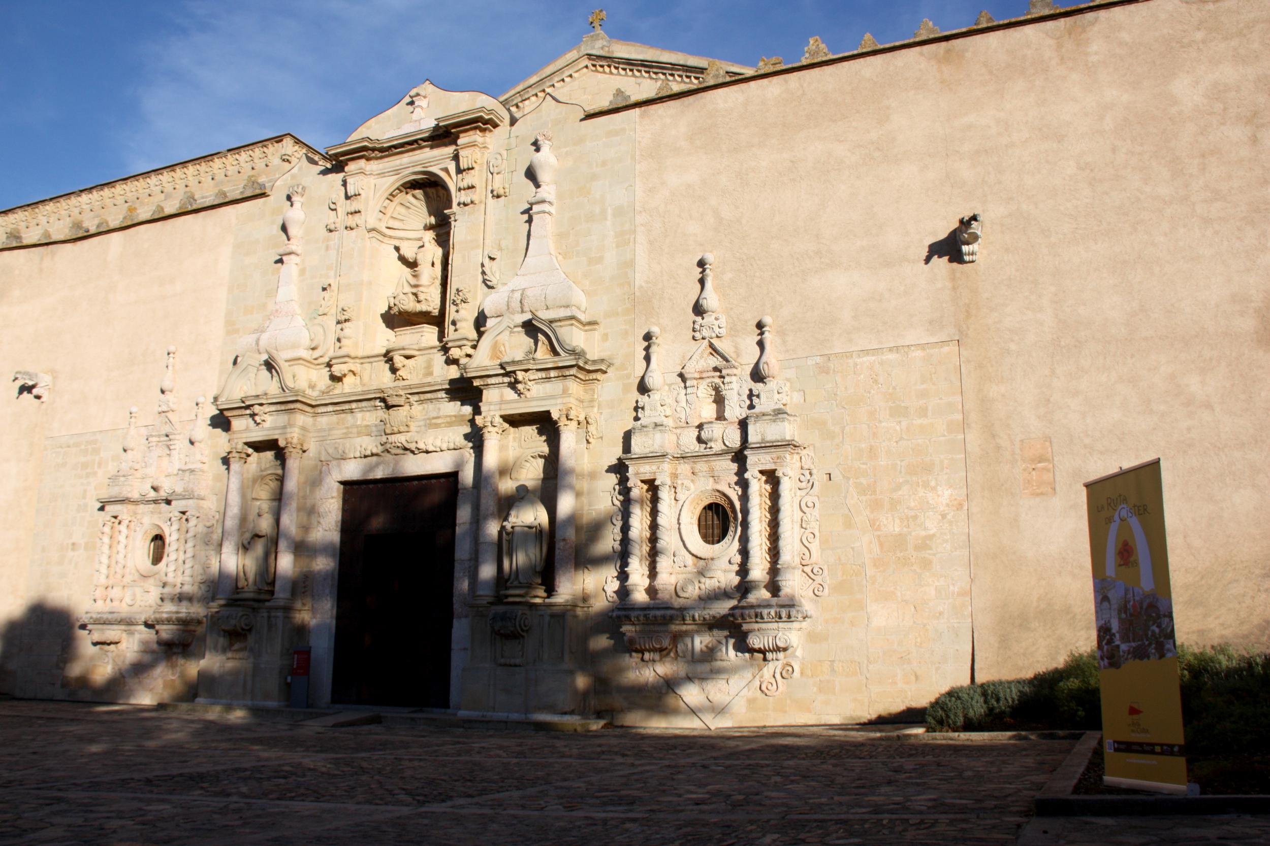 Exterior de l'església del Monestir de Poblet, amb un cartell de La Ruta del Cister a la dreta / ACN