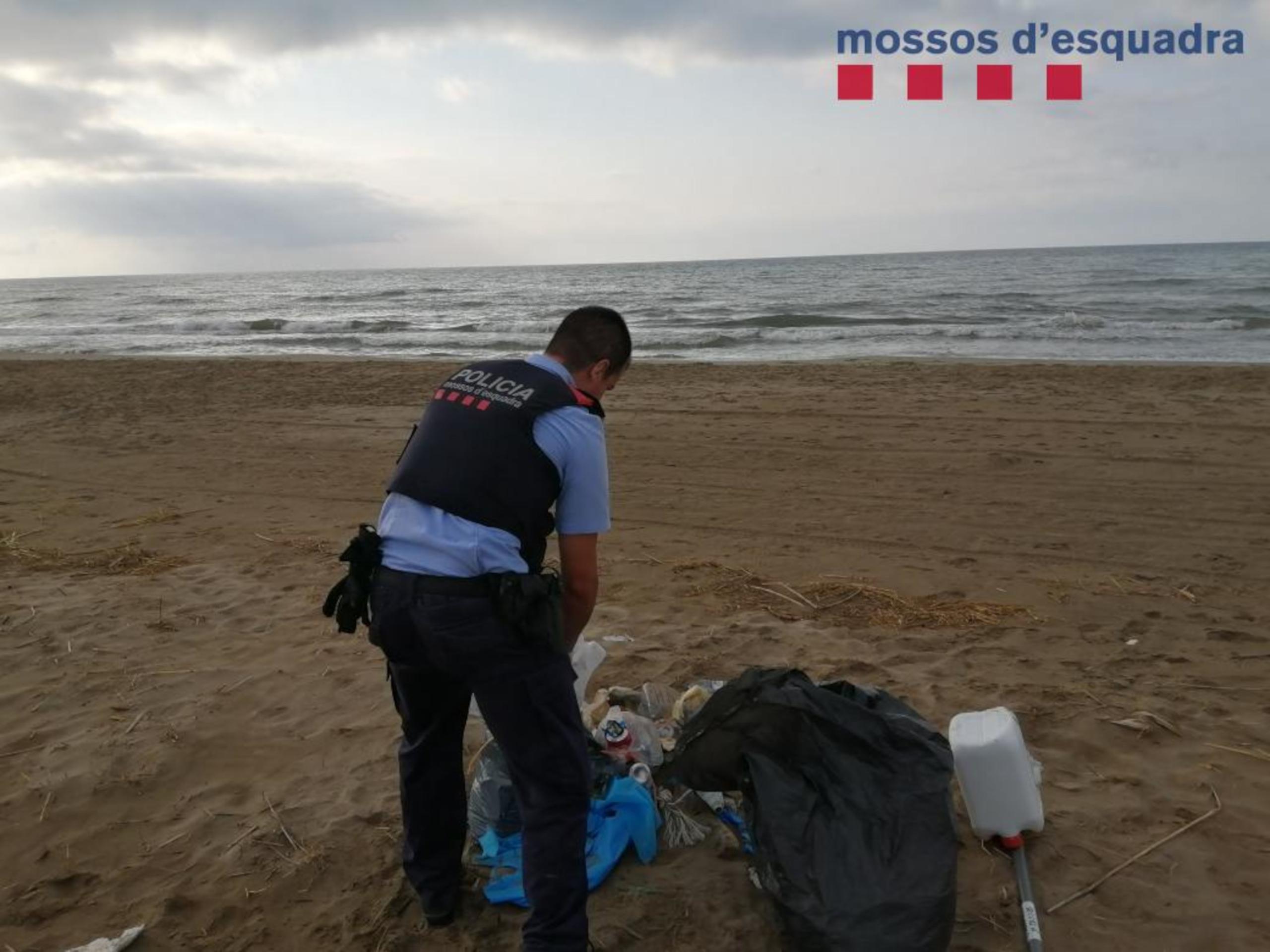 Un agent dels Mossos recollint les escombraries abocades a la Platjola dels Muntells (ACN)