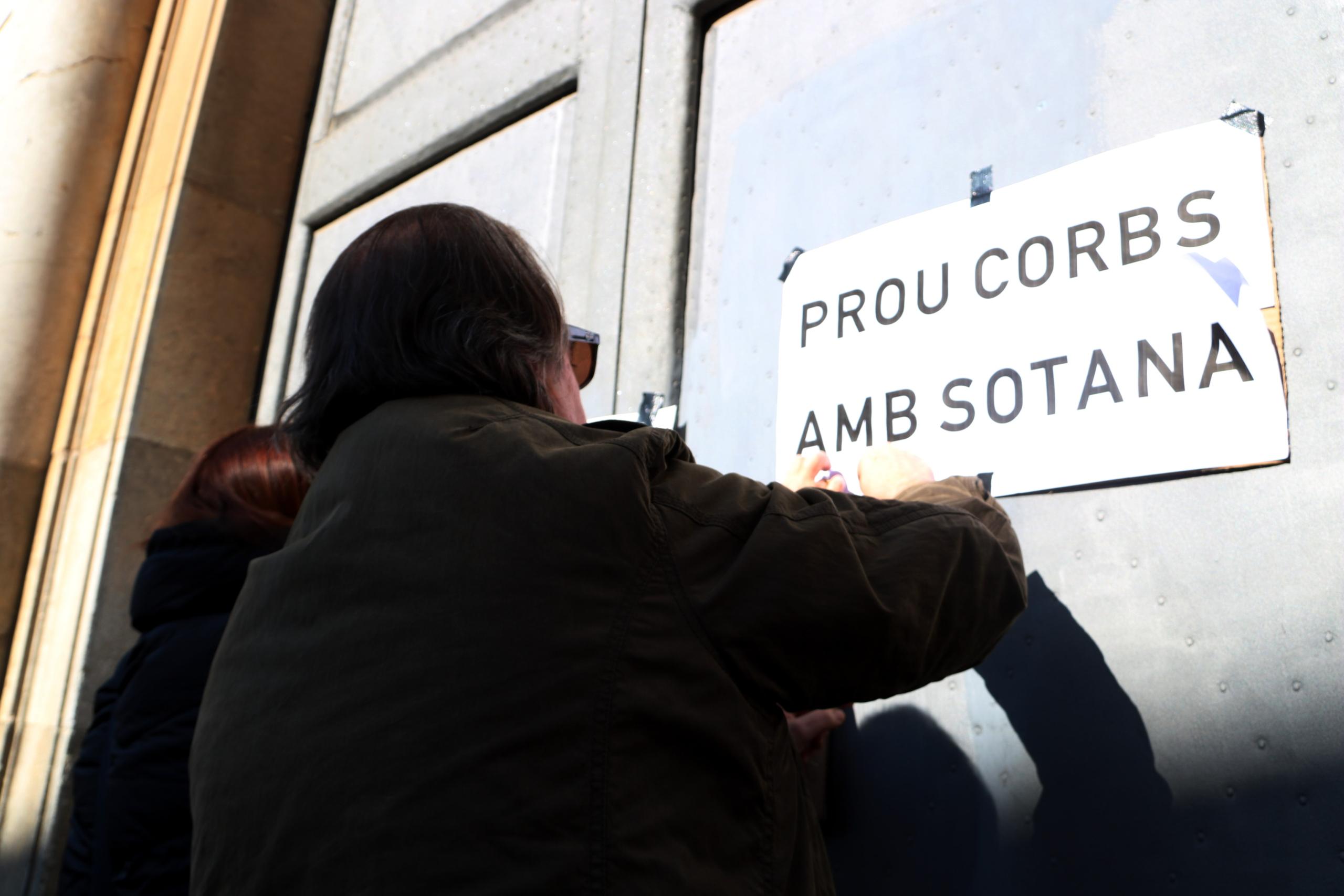 Un home enganxa cartells a les portes de l'Arquebisbat de Tarragona en la protesta per denunciar els abusos sexuals a menors (ACN)