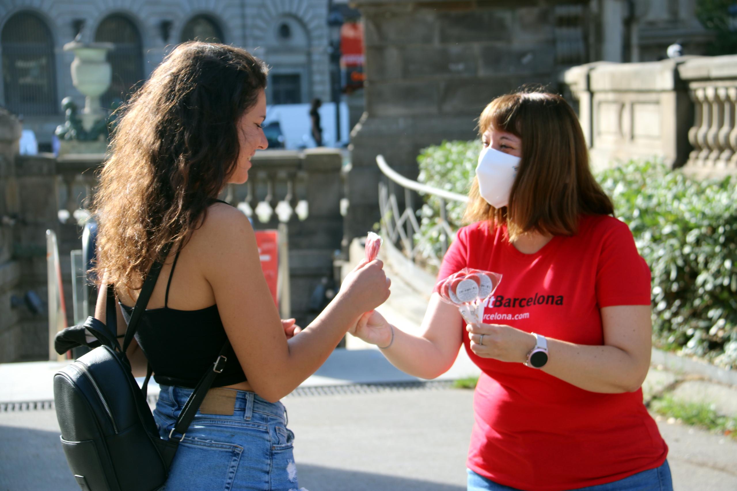 Una persona de Turisme de Barcelona repartint piruletes en forma de cor, en el marc de la nova campanya de l'entitat per demanar civisme als visitants (ACN)