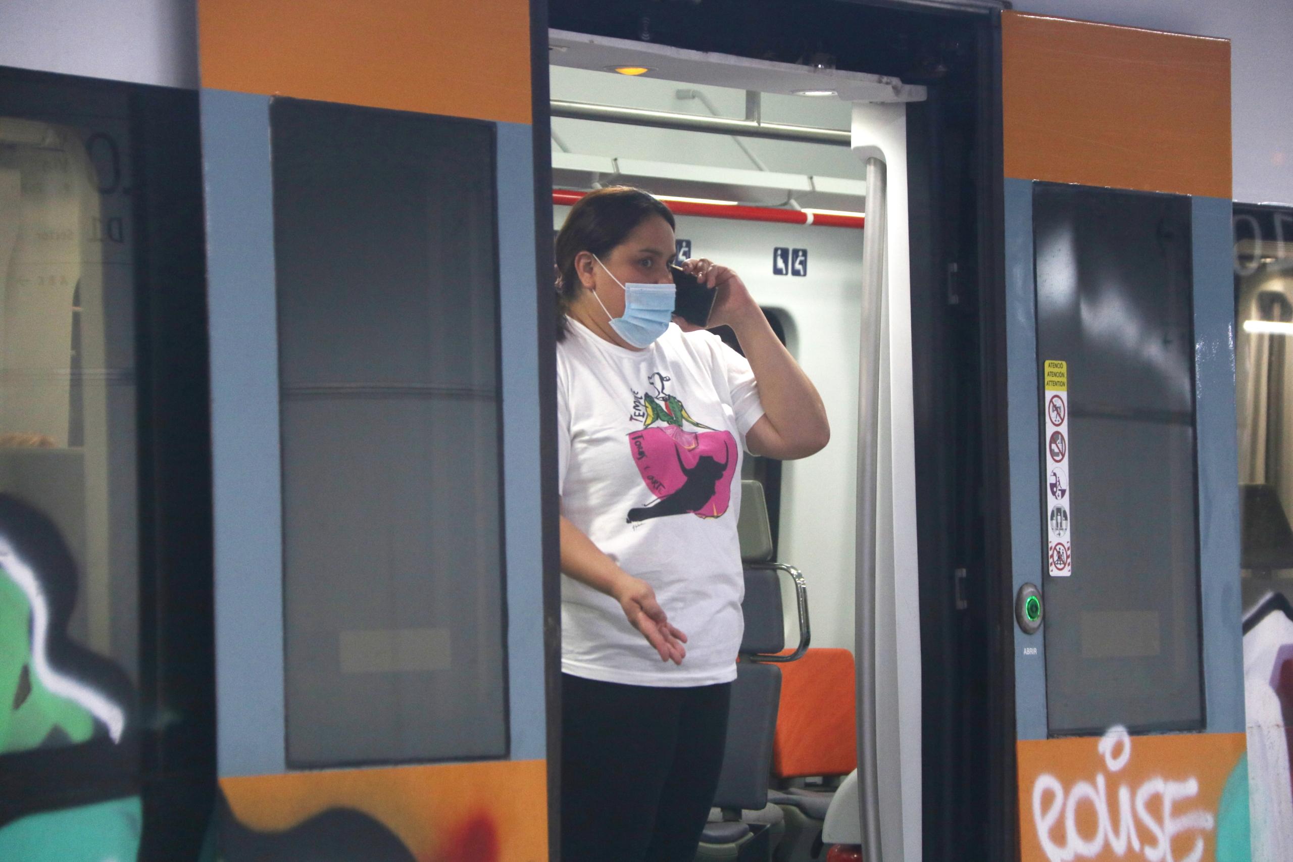 Una usuària de Rodalies trucant per telèfon mentre espera que el seu tren surti de l'estació de Sants, durant la vaga dels maquinistes de Renfe   ACN
