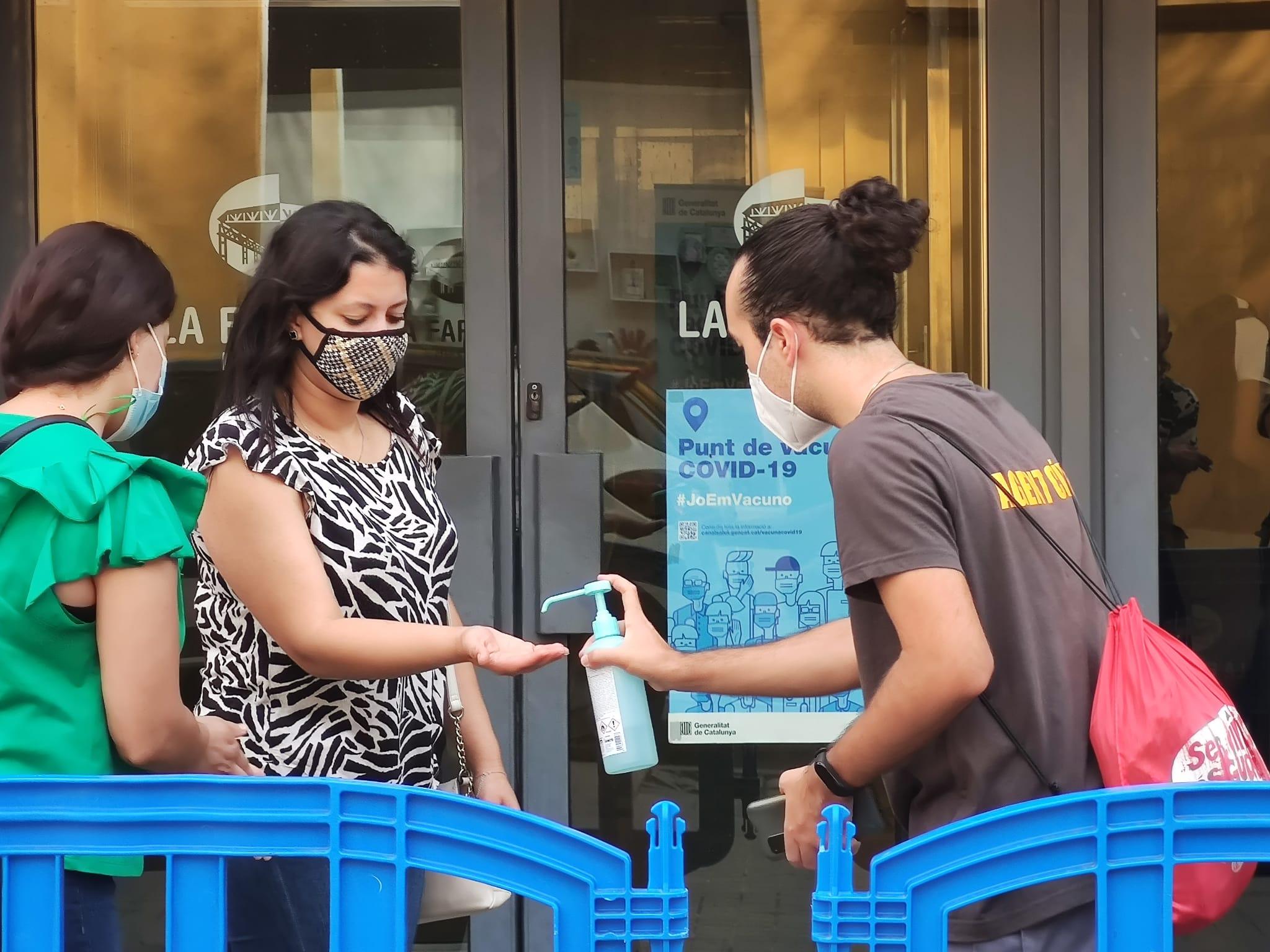 Un agent cívi posa gel hidroalcohòlic a una noia a les portes d'un punt de vacunació a L'Hospitalet de Llobregat / JAG